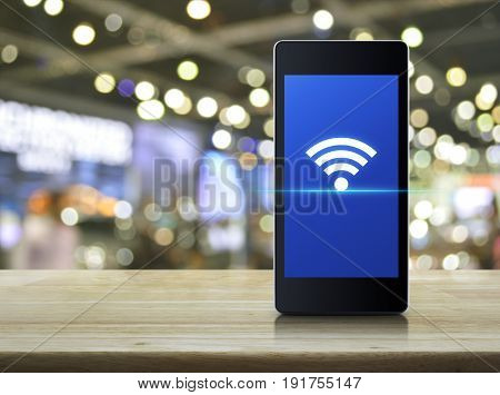 Wi-fi connection icon on modern smart phone screen on wooden table over blur light and shadow of mall Technology and internet concept