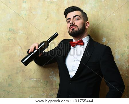 Bearded Boss With Curious Face Expression Holds Bottle Of Wine