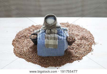 Traditional textile doll on a heap of buckwheat. Close up