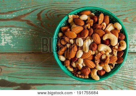 Mixed Nuts On A Turquoise Plate On A Turquoise Wooden Background.