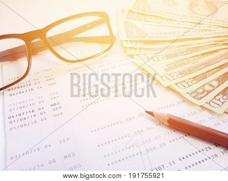 Business, finance, savings, banking or  loan concept : Pencil, eyeglasses, money and savings account passbook or financial statement on white background