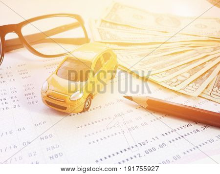 Business, finance, savings, banking or car loan concept : Miniature car model, pencil, eyeglasses, money and savings account passbook or financial statement on white background