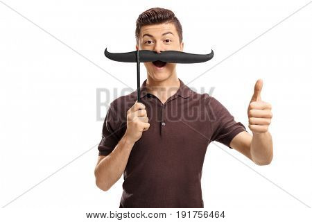 Teenage boy with fake moustache making a thumb up gesture isolated on white background
