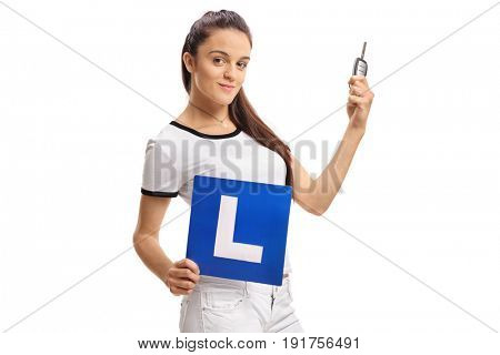 Teenage girl holding a car key and an L-sign isolated on white background