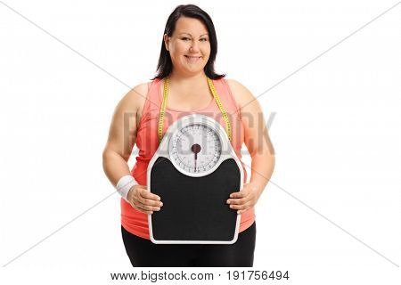 Overweight woman holding a weight scale and looking at the camera isolated on white background