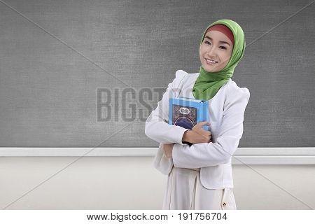 Pretty asian muslim woman holding the holy book Koran with blackboard background