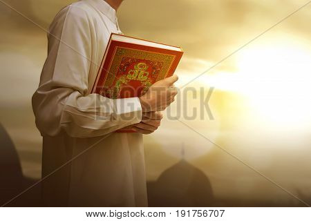 Muslim Man In Traditional Dress Holding Holy Book Koran