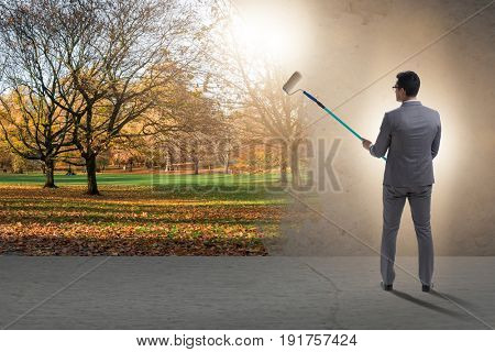 Businessman painting nature picture with roller brush