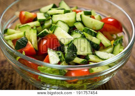 Salad with plenty of cut vegetables on glass bowl on rustic wooden table, closeup