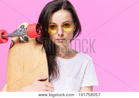 Woman in glasses, sportswoman, woman with skateboard, woman on pink background.