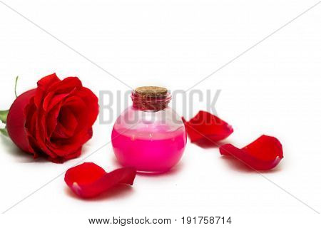 rose oil with rose petals isolated on white background