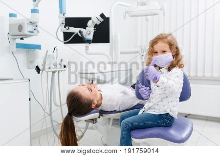 Cute little girl playing dentist sitting and gesturing thumb up looking at camera and making examination of female doctor lying in chair in clinic. Dentist office. Little girl in the dentists office