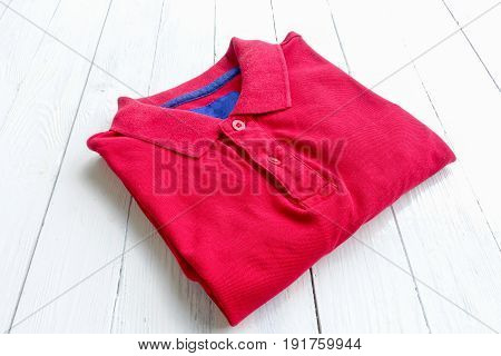 Top view of polo shirt put on wooden table background