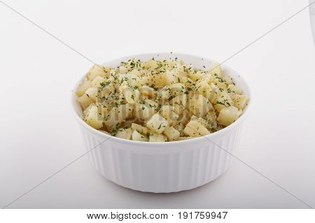 A white casserole dish full of cooked potatoes garnished with parsley