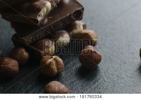 Chocolate Bar Pieces And Nuts On Dark Background With Copy Space. Chocolate Background. Toned