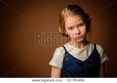 Portrait of a cute eight year old girl with sad calm look. Childhood concept.