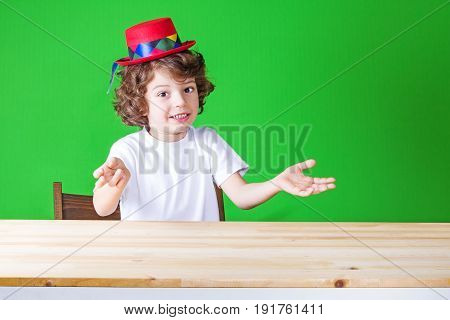 Little Curly Boy In A White Shirt And A Crimson Hat Clown Gesturing Enthusiastically Says, And Looks