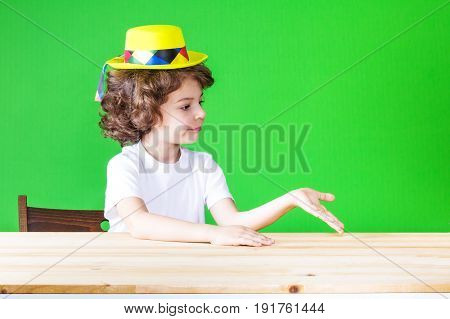 Little Curly Boy In A Yellow Clown Hat Turned His Right Hand Palm Up Looking At Her. Close-up. Green