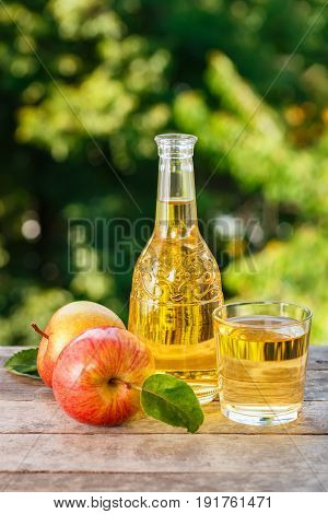 apple cider or juice in glass decanter with ripe fresh apples on wooden table with green natural background. Vertical shot. Summer drink