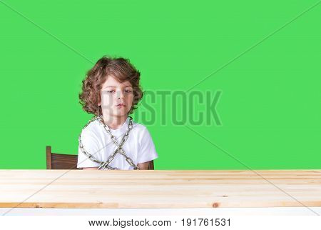 Offended Little Curly-headed Boy In A White Shirt Sits At A Table Chained To A Chair, Looking Sadly