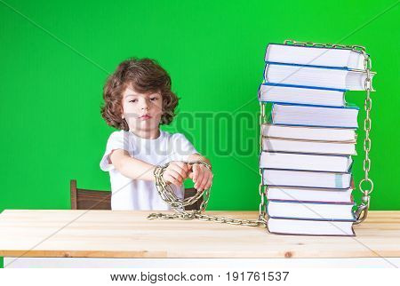 Offended Little Curly-headed Boy In A White T-shirt Stretched Out His Hands Chained To The Books. Cl