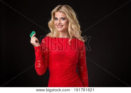 Young beautiful blond woman in a red dress with poker chips over black. Poker
