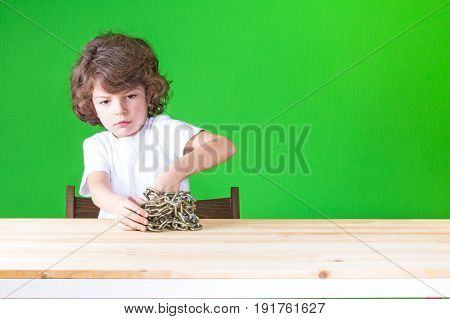 Little Curly Boy In A White T-shirt Hands-free From The Chains, Sitting At The Table. Close-up. Gree