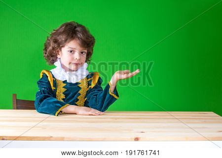 Cute Little Prince Sitting At A Table Holding In His Left Hand An Imaginary Thing, Looking At The Ca