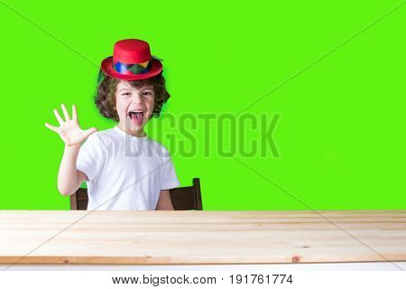 Little curly boy in a white t-shirt and a crimson hat clown sitting at the table his tongue hanging out showing five fingers and looking at the camera. Close-up. Blue background.