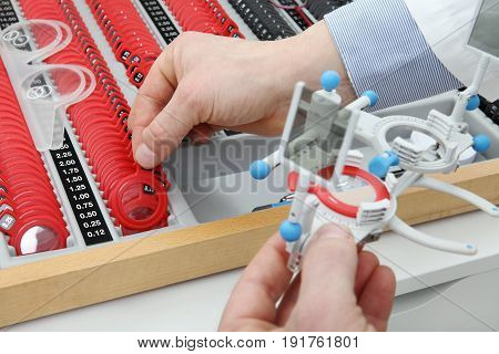 optician hands choose lenses trial frame box instrument