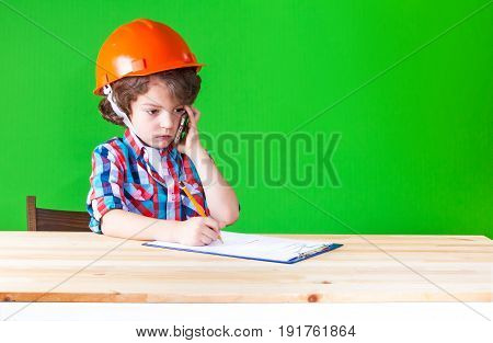 Serious little foreman wrote in pencil in a notebook with a phone in his hand. Close-up. Green background.