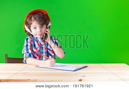 Little Curly Foreman Holding A Phone, Smiling, Writing In Pencil In A Notebook Looking At The Camera