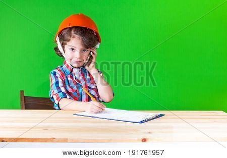 Young Cute Superintendent In A Helmet Speaks On The Phone, Writing In Pencil In A Notebook Looking A