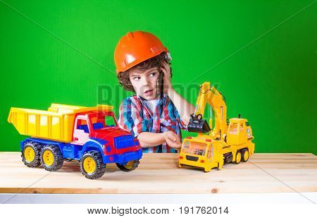 Little Curly Foreman Manages The Toy Excavator, Talking On The Phone. Close-up. Green Background.