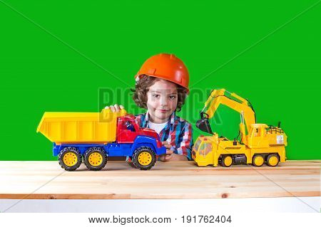 Little Curly Foreman In Helmet Playing With Construction Equipment, Looking At The Camera. Close-up.