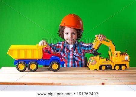 Little Curly Foreman In Helmet Playing With Construction Equipment. Close-up. Green Background.