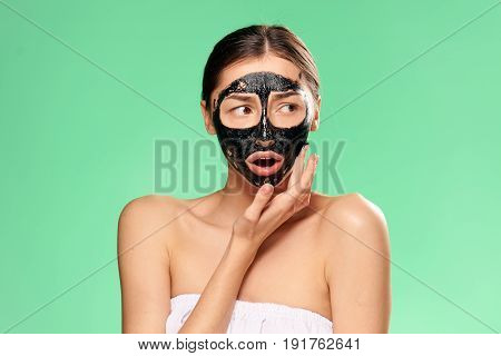 Problem with skin, woman in cosmetic mask, woman looks after face on green background.