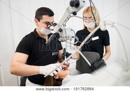 Male Dentist And Female Assistant Checking Up Patient Teeth With Dental Tools - Microscope, Mirror A