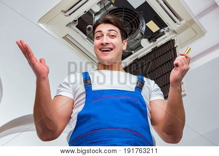 Worker repairing ceiling air conditioning unit