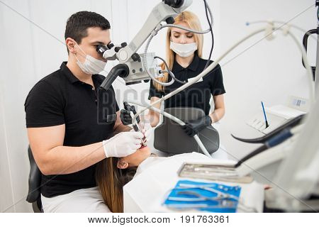 Male Dentist And Female Assistant Treating Patient Teeth With Dental Tools - Microscope, Mirror And