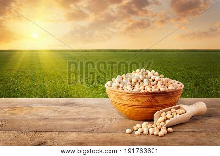 uncooked chickpeas grains in ceramic bowl on wooden table with field of chickpeas on the background. Agriculture and harvest concept. Photo with copy space. Green field on sunset