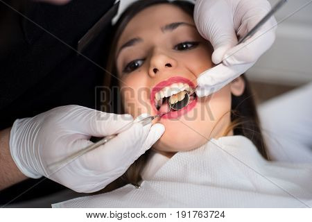 Close Up Of Beautiful Girl Having Dental Check Up In Dental Clinic. Dentist Examining A Patient's Te