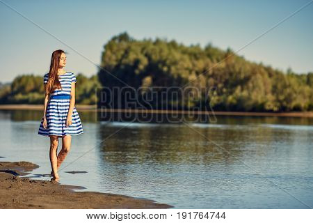 Beautiful Young Woman In Sailor Striped Dress Posing On River Bank