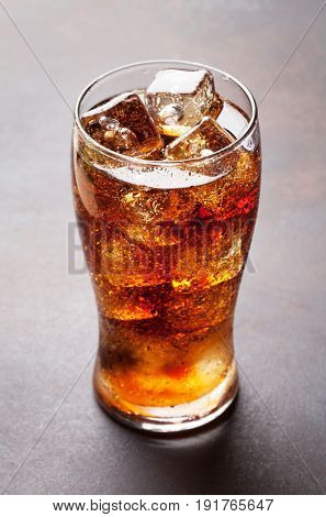 Fresh cold cola with ice on dark stone table