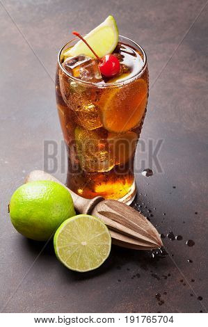 Cuba libre cocktail glass on dark stone table