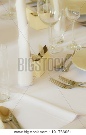 Detailed closeup of white tableware cuttlery and wedding decorations on table. Bridal decor concept.