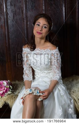 Pretty young bride playing with her garter