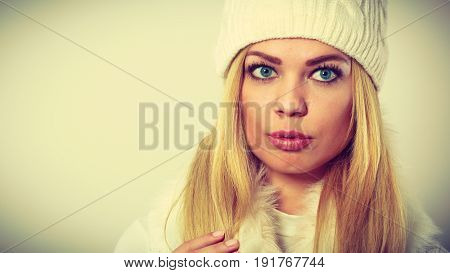 Winter fashion. Young blonde woman wearing fashionable wintertime clothes white fur scarf woolen cap and gloves studio shot