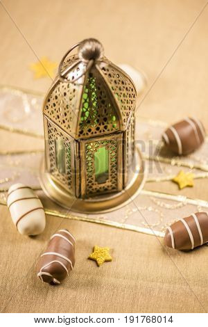 Golden traditional lamp and date chocolates. Eid confetti and decoration. An Islamic festival background.