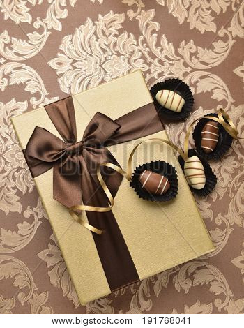A golden gift box and Arabic date chocolates. View from top.